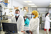 Scientists in face masks working at computer in laboratory