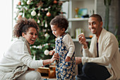 Happy parents and baby daughter decorating Christmas tree