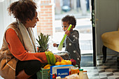 Cute baby daughter helping mother unload grocery delivery