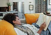 Serene woman reading book on living room sofa