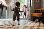 Cute baby girl in star pyjamas walking to mother
