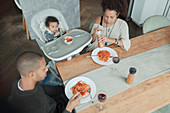 Family eating spaghetti at dining table and high chair