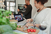 Family cooking and video chatting at digital tablet