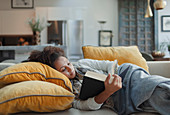 Woman relaxing and reading book on living room sofa
