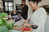 Happy woman cooking and video chatting at digital tablet