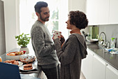 Happy couple talking in morning kitchen