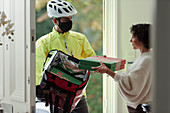 Woman receiving pizza delivery in face mask