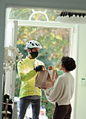 Woman receiving food delivery in face mask