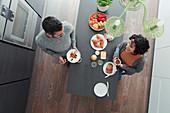 Couple talking and enjoying breakfast at kitchen island