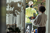 Woman receiving grocery delivery in face mask at door