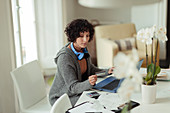 Woman with credit card paying bills at laptop