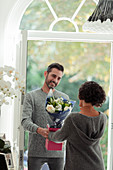 Happy husband surprising wife with flowers at front door