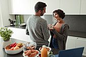 Couple enjoying breakfast and coffee in morning kitchen