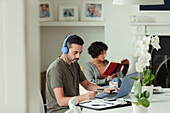Man with headphones and credit card paying bills at laptop