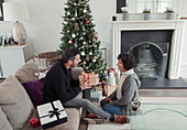 Husband giving Christmas gift to wife by tree