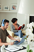 Couple reading and paying bills online at home