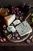 Cheese board with grapes, walnuts, apricot jam and glass of red wine (manchego, brie and blue cheese)