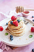 Pancakes with honey and blueberries and raspberries