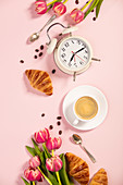 Morning coffee, croissants, alarm clock and tulips