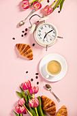 Morgenkaffee, Croissants, Wecker und Tulpen