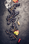 Wineglasses with grapes and corks on dark background