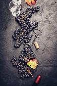 Weingläser mit Trauben und Korken auf dunklem Hintergrund