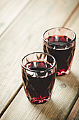 Two glasses of red wine on wooden background