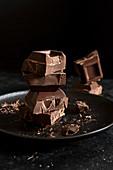 Stapel von Schokoladenstücken auf schwarzem Hintergrund