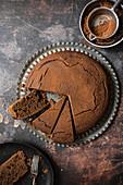Schokoladenkuchen mit Sieb und Kakaopulver