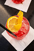 Campari soda with ice cubes and a lemon slice