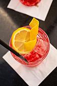 Campari Soda mit Eiswürfeln und Zitronenscheibe