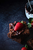 Brownies with melted chocolate and strawberries.