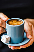 Hands holding Turkish coffee with turkish delight
