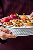 Hände halten Apfel-Zimt-Muffins