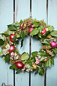 Autumn wreath with moss, ivy leaves, red onions, hydrangea blossoms, snowberries and chestnut shells