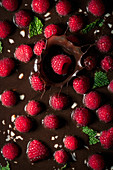 Raspberry falling into chocolate dessert