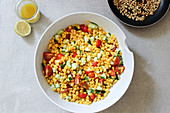 Sweetcorn salad with tomatoes, cucumber and pine nuts