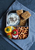 A breakfast box with muesli bars, stuffed snack peppers and chickpeas