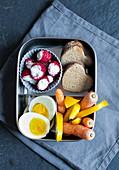 Frühstücksbox mit Brotherzen, Gemüsesticks, Ei und gefüllten Himbeeren