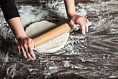 Rolling bread dough on table sprinkled with flour