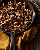 Knuspermüsli mit Nüssen und Honig in der Pfanne