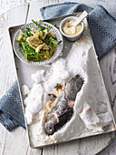 Salt-crusted trout with artichoke salad and aioli