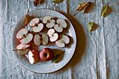 Rote Äpfel ganz und halbiert auf Teller