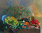 Still life with a chilli plant, various chilli peppers, chilli powder, harissa