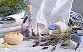 Wellness-Stillleben: Duftöle, Lavendelseife, Badesalz, Naturschwamm, Lavendelblüte