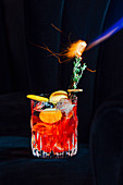 Negroni cocktail with orange slices and burning sprig of rosemary