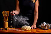 Female sprinkling kneaded bread dough with flour