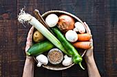 Hände halten Korb mit Gemüse und einem Glas Getreide