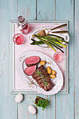 Fillet of beef with roasted asparagus and potatoes on tray