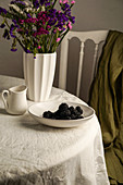 Blackberry in a white bowl on the linen clothtable
